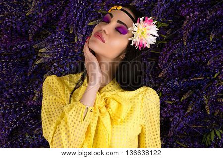 beautiful woman on background lupine flowers in studio