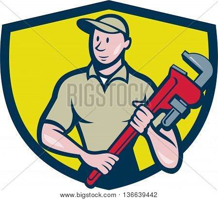 Illustration of a plumber in overalls and hat standing looking to the side holding monkey wrench viewed from front set inside shield crest on isolated background done in cartoon style.