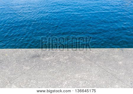 Half concrete wall and blue water background