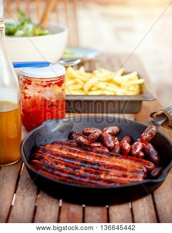 Tasty fried pork sausages from the grill, french fries and sauce on the table, barbecue picnic outdoors, delicious unhealthy food