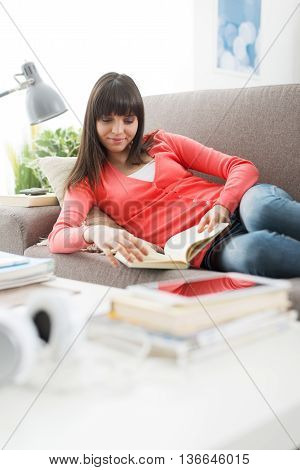 Smiling young woman relaxing at home on the couch and reading a novel leisure and relaxation concept