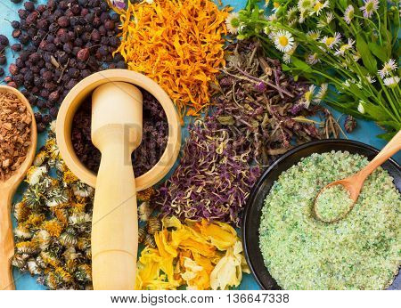 A set of dried flowers and berries herbs oak bark sea salt on old wooden table. Alternative medicine homeopathy