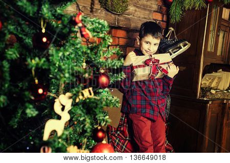 Family celebration of the New Year. Boy near a Christmas tree. Giving gifts. Holiday and fun.