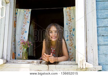 Laughing joyful little girl looks out from the window wide open