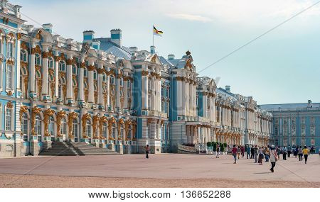 Saint-Petersburg, Russia - June 26, 2016: The main facade of the Catherine Palace in Tsarskoye Selo. Tourists sightseeing. On the roof of the royal flag is developing.