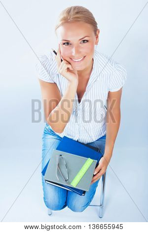 Portrait of beautiful serious teenage girl sitting on the lesson, isolated on blue background, passing exam, back to school, time to study