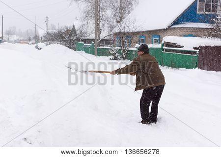 elderly man clears snow near the house