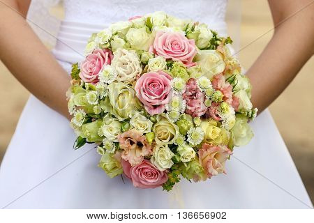 The bride's bouquet on the background of the dress.