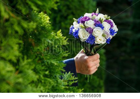 beautiful wedding bouquet in hands of men.
