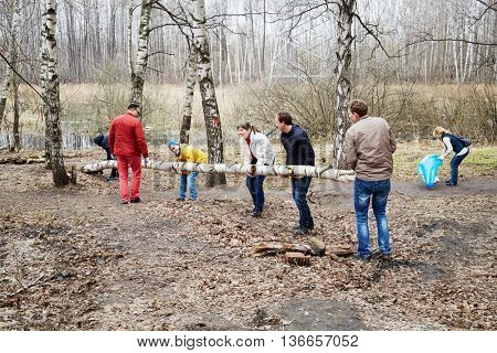 MOSCOW, RUSSIA - APR 18, 2015: People carry big tree trunk during cleaning works at Elk Island residential complex. More than 2.5 million people participate in annual cleaning work in Moscow.