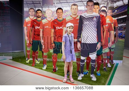 MOSCOW, RUSSIA - MAY 26, 2015: Girl with photos of team players in full length at the Locomotive soccer club museum. Museum was opened on November 24, 2011.