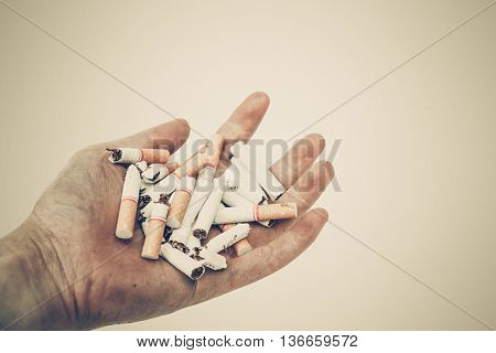 Stop smoking - Hand of a smoker holding destroyed cigarettes - World no tobacco day concept