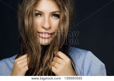 Happy Girl Holds Hands Hair On A Blue Background. Woman Smiling And Looking At The Camera