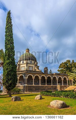 The Middle East, Sea of Galilee. The dome of basilica is surrounded by a gallery with columns.  Thick midday shadows of palms and cypresses