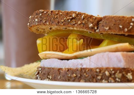 Ham sandwich on multi-grain with cheese and peppers