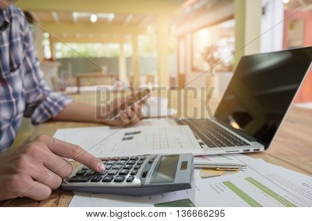 business man using a calculator in coffee shop
