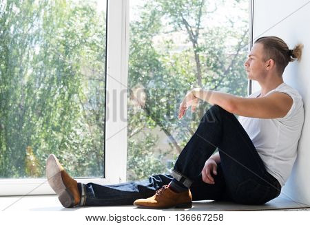 Handsome young man sitting on windowsill