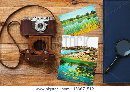 Vintage very old film camera magnifying glass foto and photo album on brown wooden background and space for text.