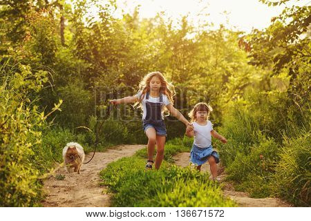 Little sisters and pet. Girls and dog running along the road in the city park. Hand in hand. Pedigree dogs Spitz.