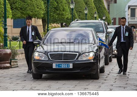 BANGKOK THAILAND - NOVEMBER 17 2013 : An unidentified body guards protect state automobile which moves in the Grand Palace in Bangkok.