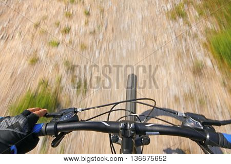 Detail of a mountain bike on a dirty and gravy rural road. View from above.