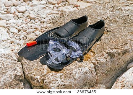 Beach accessories. Mask fins snorkel on Seastone
