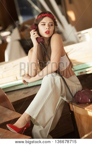 pretty woman talking on old telephone. Fashion model. Red lips. Sunny color.