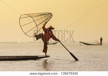 INLE LAKE MYANMAR - JANUARY 12 2016: Unidentified Burmese fisherman on bamboo boat catching fish in traditional way with handmade net. Inle lake Myanmar Burma