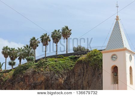 Steeple of the parish church in Camara de Lobos and mound of rock with palm trees on the island of Madeira