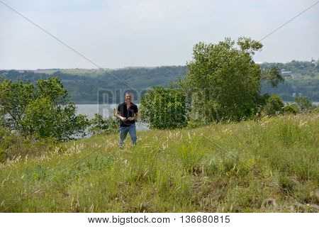 Mature man of a harmonious constitution is walking on the wild grass of Dnieper riverbank in bright light of spring sun.