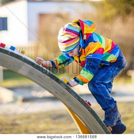 Adorable kid boy having fun on outdoor playground. child climbing on scaffolding on warm sunny spring or autumn day. Active leisure with kids. Boy wearing colorful clothes