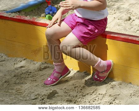 Part of the image of a little girl sitting on the edge of the rim of a child's sandbox. The girl in the hot day resting in the shade.