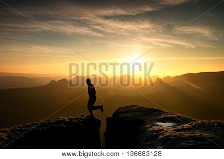 Hiker In Black Is Jumping Between Mountains Peaks.