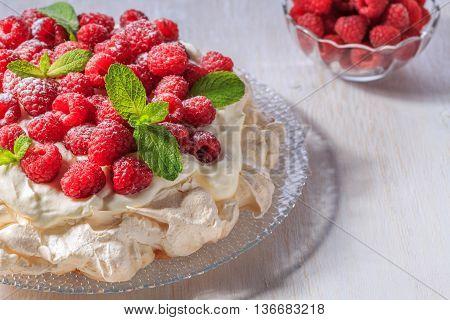 Meringue Pavlova with whipped cream and fresh raspberries selective focus.