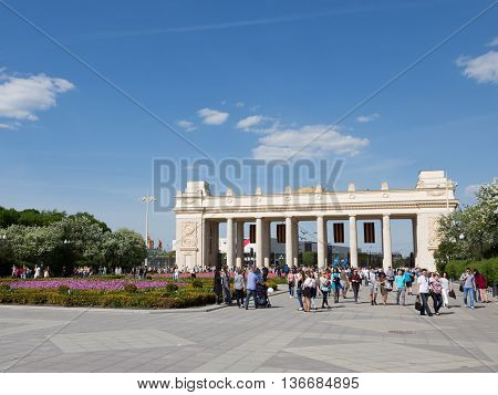 spring young beautiful go Moscow girl people entrance to the park St. George's ribbons the crowd Soviet architecture May holidays holiday Gorky Park happiness patriotism pride lawn Victory Day city park Russia rest in the park walking hiking sightseeing v