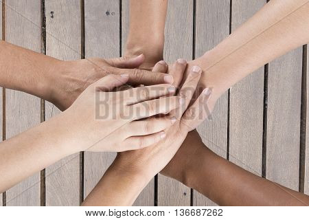 People Put Hand Together On Wooden Table For Use As Teamwork Concept