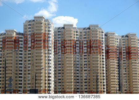 Top section of modern apartment building constructed from bricks over clear blue sky with white clouds on summer day