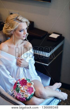 Beauty Bride In Dressing Gown With Bouquet Indoors. Beautiful Model Girl In Colorful Wedding Robe. F