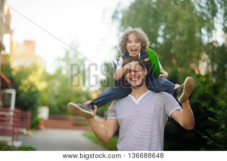 Little schoolboy sitting on the shoulders of his father. The boy by the hand closes the eyes of the father. He likes to joke with dad. Father and son smiling happily. Back to school