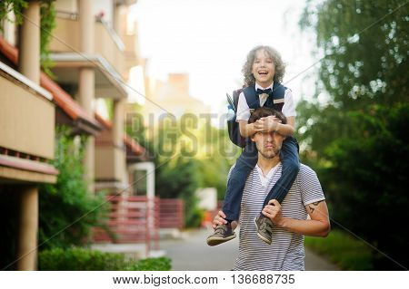 Little schoolboy sitting on the shoulders of his father. The father holds the boy's legs. The boy delighted. He likes to joke with dad. Son happily smiling and father jokingly serious.