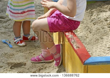 Part of the image of a little girl sitting on the edge of the rim of a child's sandbox. The girl in the hot day resting in the shade. Standing next to another child.