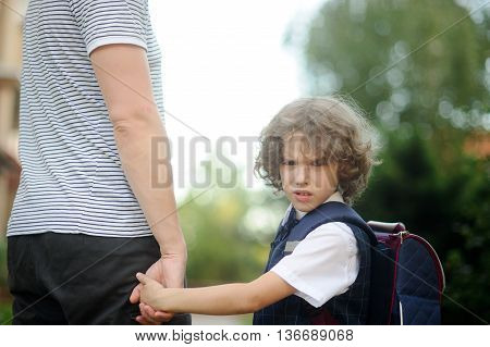The father conducts the son-first-grader in school. He holds his son's hand. The boy turned and looked into the camera with an angry expression on his face.