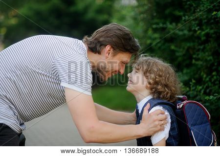 The father sees his son at school first-grader. He leaned over to the boy and took him by the shoulders. Father and son look at each other with love and smile.