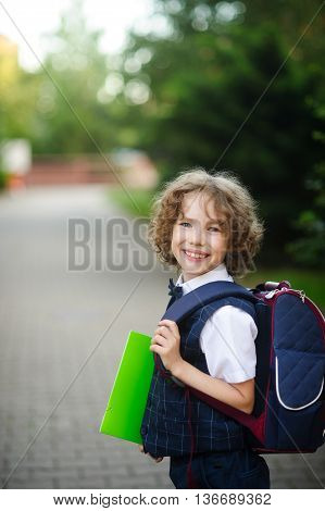 The little curly haired boy stands in the courtyard of the school. The boy's cute face. Behind the backpack in the hands of bright green folder. Schoolboy looks into the camera and smiles.