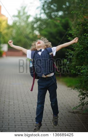 Little schoolboy as if flying. The boy spread his arms his face raised to the sky.