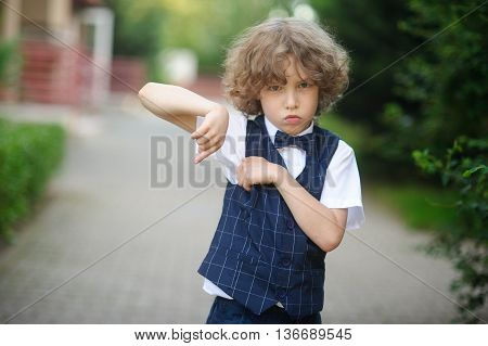 Little pupil is in the schoolyard with an angry expression on his face. The boy has blond curly hair and blue eyes. He is angry and showing something with his hands.
