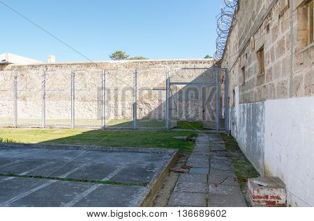 FREMANTLE,WA,AUSTRALIA-JUNE 1,2016:  Gated isolate yard at the Fremantle Prison under a clear blue sky in Fremantle, Western Australia.