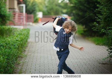 Small pupil in the school yard . The boy angrily waving his backpack .