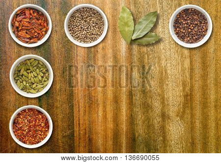 Spices including chilli flakes cloves bird's eye chillies cardamoms bay leaves and coriander seeds in white pots on an old dark wood chopping board with copy space