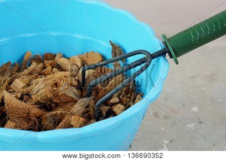 A Gardening Trowel and Pieces of coconut coir husk in plastic pot